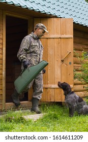 a hunter with a gun case in his hand and a dog come out of the door of a wooden house