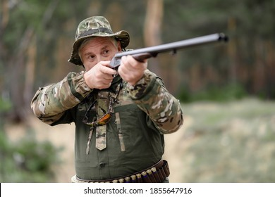 A hunter with a gun in his hands aiming at a wild animal in the forest. The hunter came to the forest to hunt.