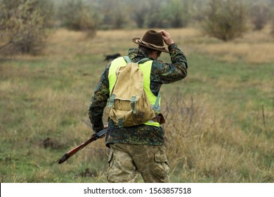 A hunter with a gun in his hands and a hunting dog in a reflective green vest hunts a pheasant in the steppe.