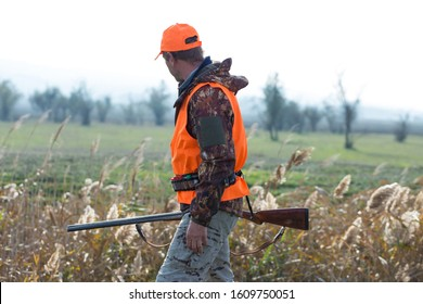 A hunter with a gun in his hands in hunting clothes in the autumn forest in search of a trophy. A man stands with weapon.