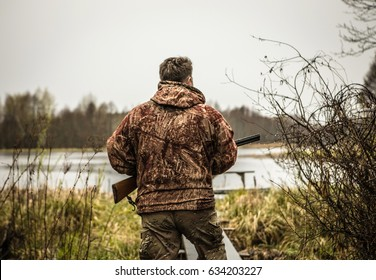 Hunter with a gun tracks down ducks on the river.