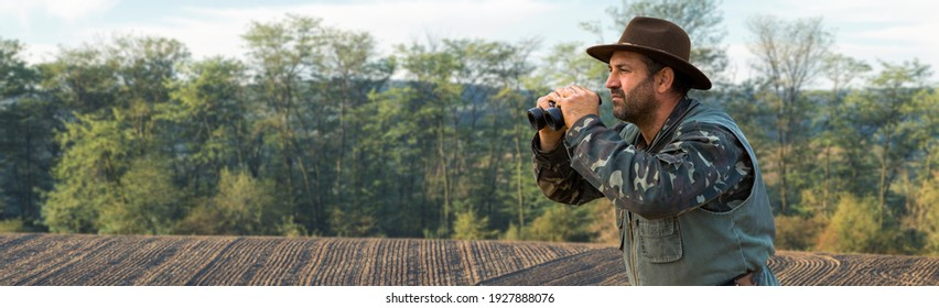 A hunter in a hat with binoculars looks out for prey against the background of the forest.