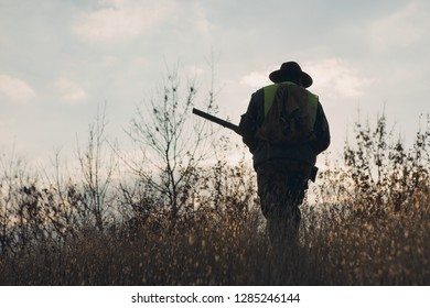 A hunter in a hat with a gun in camouflage and a reflective vest in the steppe