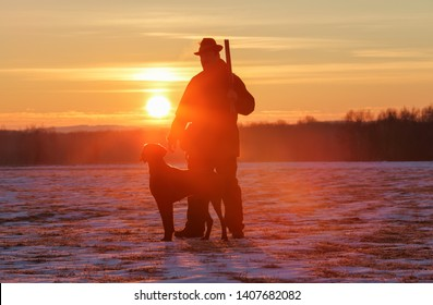 A hunter in a hat with a gun and a German shorthair pointer dog breed stands on a meadow covered with snow. Majestic winter scenery. Amazing sunrise.