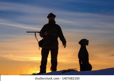 A hunter in a hat with a gun and a German shorthair pointer dog breed stands on a meadow covered with snow. Amazing sunrise.