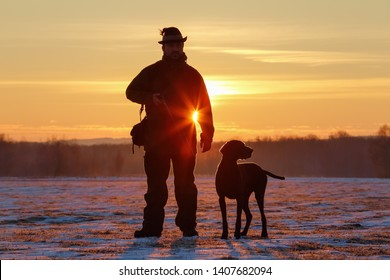 A hunter in the hat with a gun and his German Shorthaired Pointer dog breed friend. Beautiful silhouettes on the background of the dawn. Amazing winter morning.
