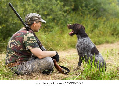 hunter with his dog resting on the mown grass during the autumn hunting
