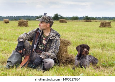 hunter with his gundog resting on the hayfield during the autumn hunting