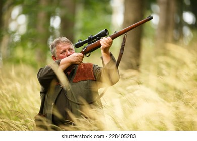 hunter with his rifle in spring forest, hunter holding a rifle and waiting for prey, hunter shooting and aiming
