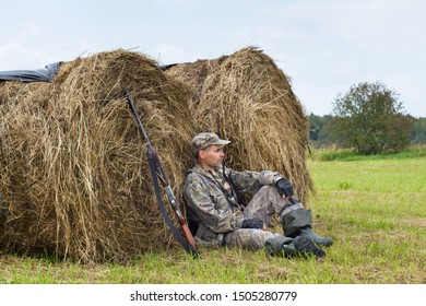 hunter with his shotgun resting on the hayfield during the autumn hunting