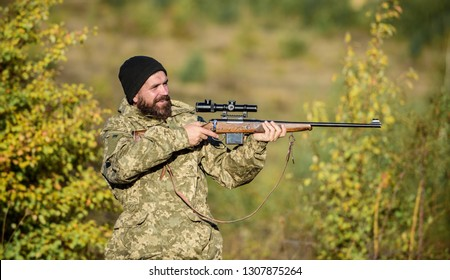 Hunter hold rifle. Bearded hunter spend leisure hunting. Focus and concentration of experienced hunter. Hunting masculine hobby concept. Man brutal gamekeeper nature background. Regulation of hunting.