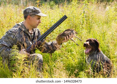 hunter holding a downed grouse, which brought the gundog (german wirehaired pointer) during hunting