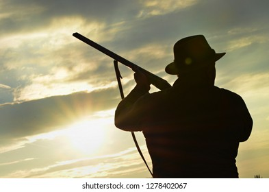 hunter holding a shotgun ready to shoot, silhouette against the sunset