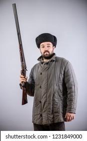 Hunter with horizontal double-barreled shotgun in hand, rifle is directed forward, retro style, studio shot