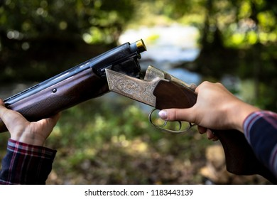 Hunter with hunting gun in the autumn forest. Woman is charging a hunting rifle. Close up.