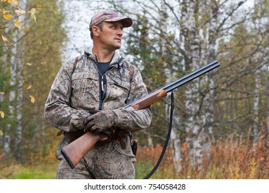 hunter with hunting gun walking in the woods in autumn