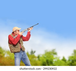The hunter with hunting rifle aiming at blue sky. Picture with space for your text.
