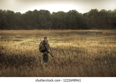 hunter hunting in  rural field nearby woodland at sunset during hunting season