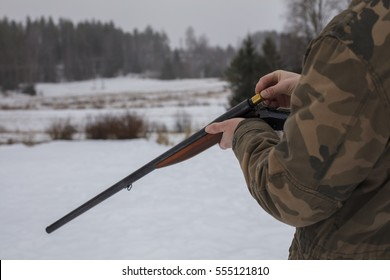 Hunter keeps a old shotgun and cartridge in his hand in Finland. Background out of focus in wintry forest landscape.