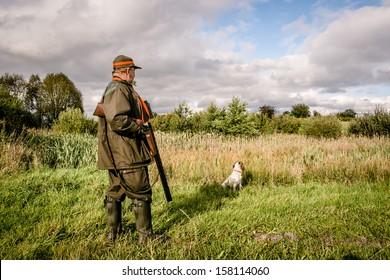 Hunter at a lake, waiting with his dog