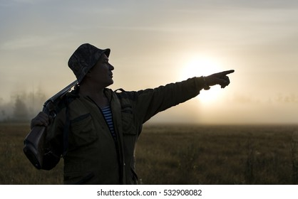 Hunter looking to horizon during a hunt at sunrise and specify the hand