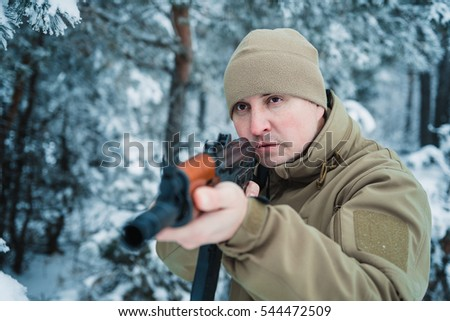 75b616ac227 Hunter man dressed in camouflage clothing in the winter pine forest. Armed  with a rifle