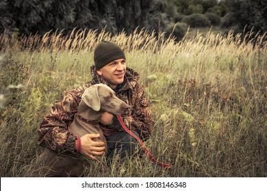 Homme de chasse avec le chien de chasse Weimaraner dans la haute herbe rurale pendant la saison de chasse