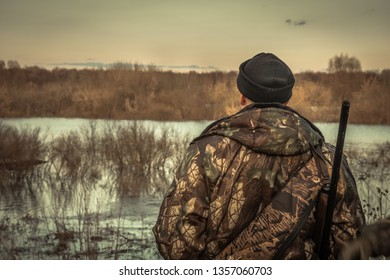 Hunter man hunting looking into the distance horizon in camouflage during hunting season rear view sunset river flood landscape