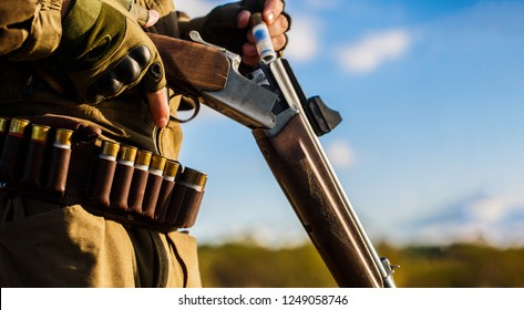 Hunter man. Hunting period. Male with a gun, rifle. Man is charging a hunting rifle. Process of hunting during hunting season. Male hunter in ready to hunt. Closeup. The man is on the hunt, sport.