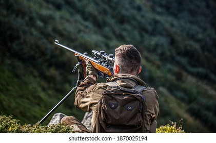 Hunter man. Hunting period. Male with a gun. Close up. Hunter with hunting gun and hunting form to hunt. Hunter is aiming. Shooter sighting in the target. The man is on the hunt. Hunt hunting rifle.