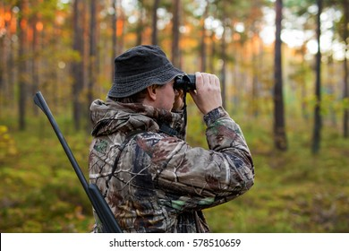Hunter observing forest with binoculars