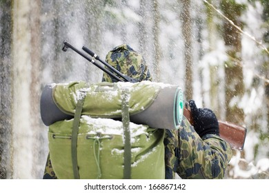 Hunter with optical rifle in winter in snowfall