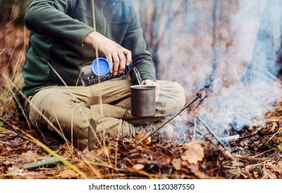 hunter pours water from a bottle into a metal mug. bushcraft, adventure, travel, tourism and camping concept.
