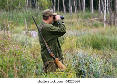Hunter with rifle and binoculars in a forest`s swamp.