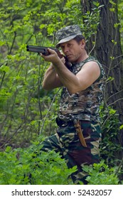 Hunter with rifle in forest