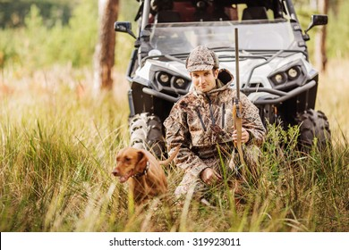 Hunter with Rifle and Four Wheeler Tire in fall forest