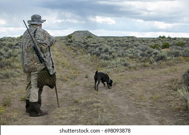 A hunter with rifle wearing camouflage following a tracking dog in a semi arid landscape in southwest Wyoming while hunting coyote.