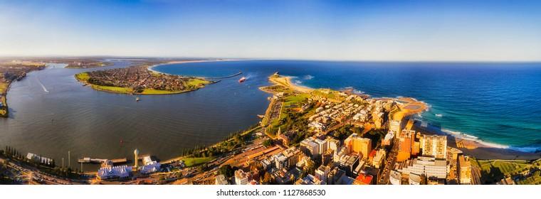 Hunter river enters pacific ocean between heads of Newcastle ciy in elevated aerial panorama of coastal region in Australia.