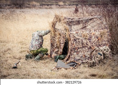 Hunter in rural field installing camouflage tent before hunting