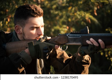 Hunter with shotgun gun on hunt. Hunter with Powerful Rifle with Scope Spotting Animals. Close up snipers carbine at the outdoor hunting