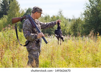 the hunter with a shotgun holds in his hand a hunting trophy - downed black grouse