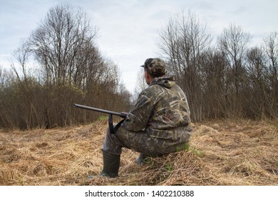 hunter with a shotgun sitting in a clearing in the bush and waiting for the evening
