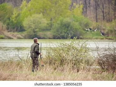 Hunter sneaking on wild ducks on a lake
