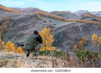 Hunter with sniper rifle is sitting one's hunkers and looking for prey through binoculars. Hunter in the mountains with sniper rifle and binoculars, trophy hunting concept.