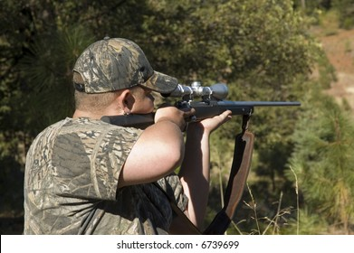 Hunter taking aim at target with rifle dressed in camouflage