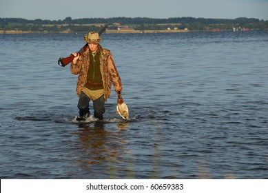 hunter wading with a duck in his hand