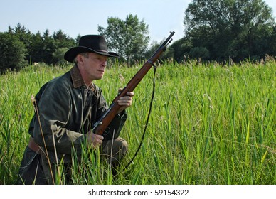 Hunter waiting in the grass with his rifle