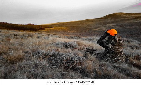 Hunter wearing camouflage and hunter orange in Wyoming high desert scoping