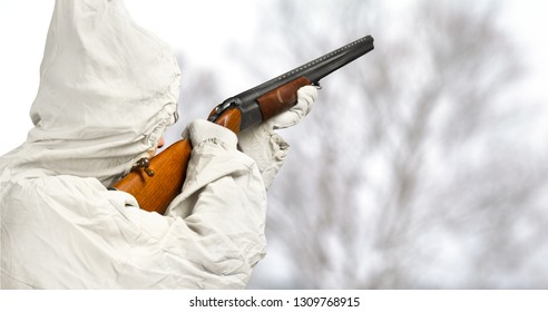 hunter in white camouflage aims a shotgun in the winter field