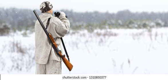 hunter in white camouflage with binoculars is in winter field
